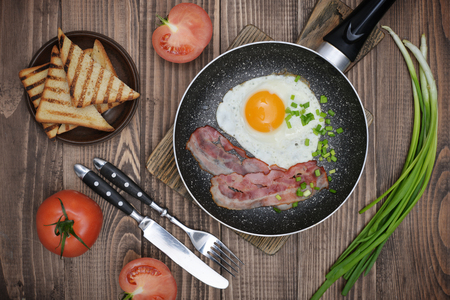 sunny side up: Bacon with sunny side up egg on pan served with  tomato and toasts  top view