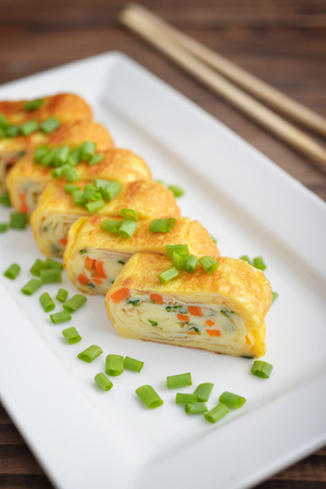 dashi: Dashimaki tamago - japanese rolled omelette on white plate on wooden background