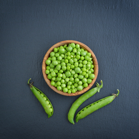 Green peas in wooden bowl on black slate background, top view