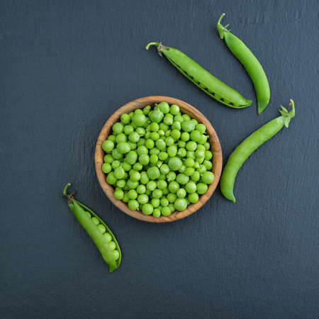 black beans: Green peas in wooden bowl on black slate background, top view