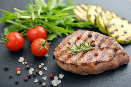 charbroiled: Grilled steak with rukkola and cherry tomato on black slate background