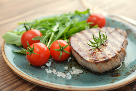 Grilled steak with rukkola and cherry tomato on wooden background