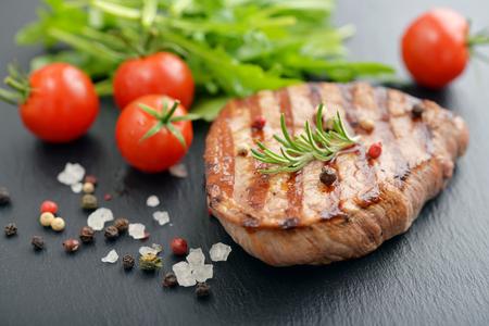 Grilled steak with rukkola and cherry tomato on black slate background