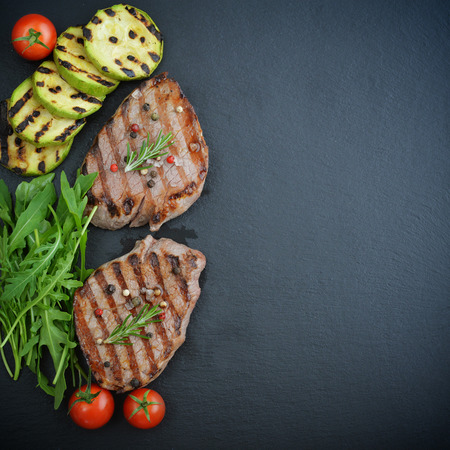 charbroiled: Grilled steak with rukkolaGrilled steak with rukkola and cherry tomato on black slate background, top view