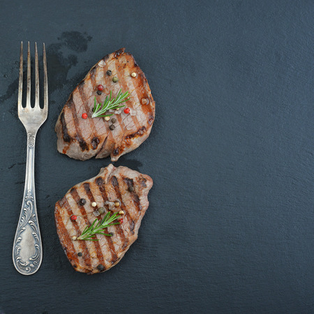 charbroiled: Grilled steak with fork on black slate background, top view Stock Photo