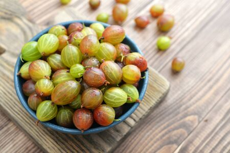 Fresh ripe gooseberries in bowl on a wooden background closeup Stock Photo