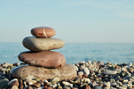 smooth stones: Stack of round smooth stones on a seashore over sea background Stock Photo