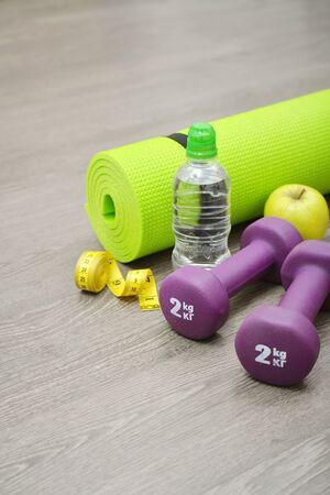 Fitness equipment: dumbbells, water,apple and mat for fitness classes on  floor Stock Photo