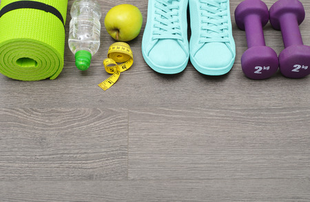 karemat: Fitness equipment: sneakers, water,apple and mat for fitness classes on  floor