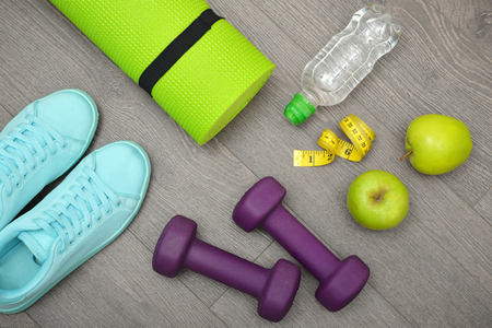 trainers: Fitness equipment: sneakers, water,apple and mat for fitness classes on  floor