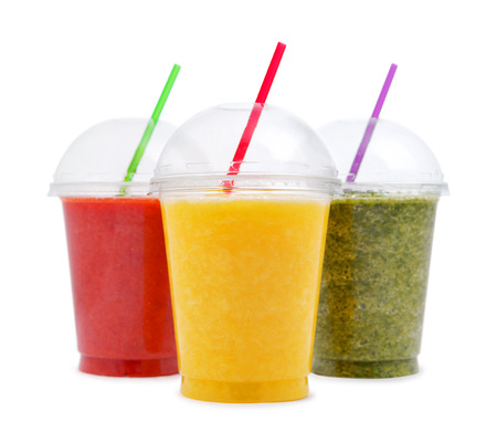 Green, orange and red smoothie in plastic transparent cups isolated on white background