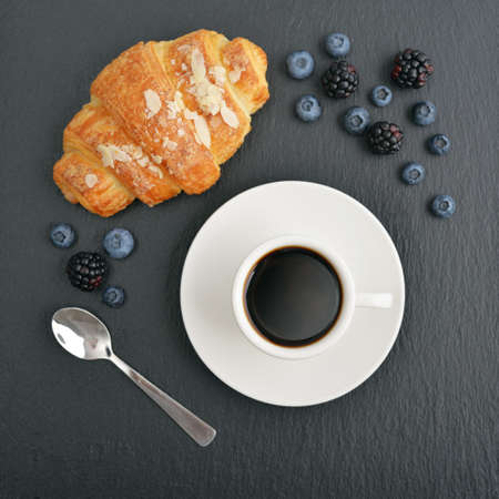 beverage menu: Croissant and coffee with fresh berries on black slate background, top view