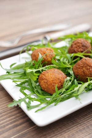 Fresh vegetarian falafel with arugula on plate closeup