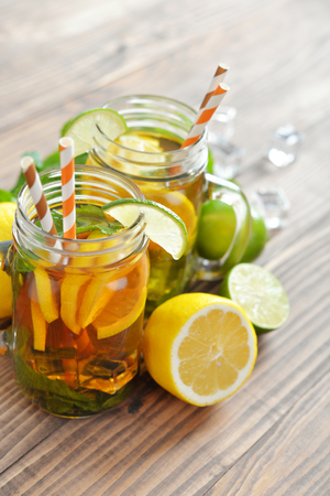 Ice tea with fresh lemons and mint on wooden background Stock Photo