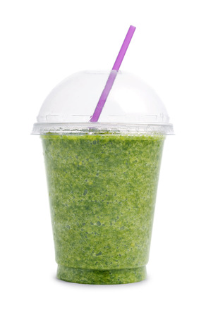 natural juices: Green smoothie in plastic transparent cup isolated on white background