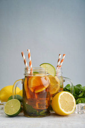 Ice tea with fresh lemons and mint on blue background
