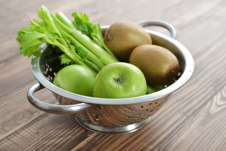 a colander: Apples, selery and kiwi in a colander on wooden background Stock Photo