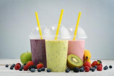 licuado de platano: batidos de frutas en copas de plástico con el arándano, fresa, kiwi, mora, frambuesa y plátano en el fondo azul. Para llevar bebidas concepto.