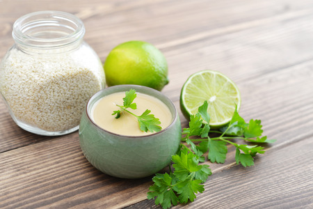 ajonjoli: Tahini made from sesame seeds in bowl with parsley on wooden background