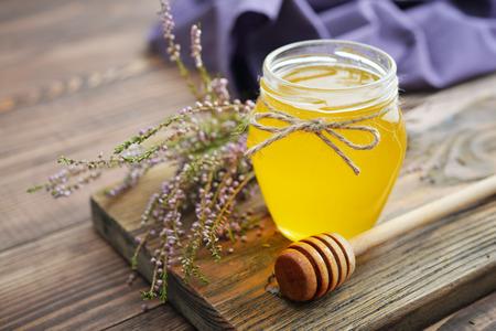木製の背景の新鮮なヒースが付いている瓶にハーブ蜂蜜