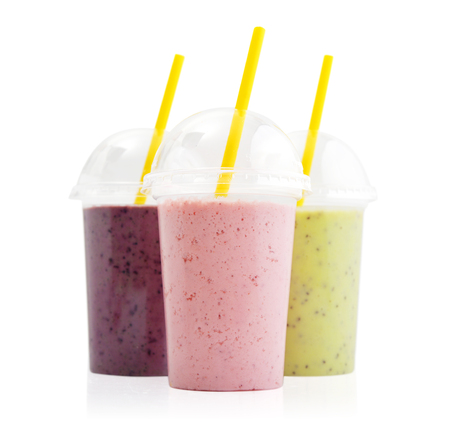 Fruit smoothies in plastic cups with blueberry, strawberry, kiwi, blackberry, raspberry and banana isolated on white background. Take away drinks concept.
