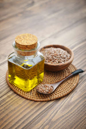 flaxseed: Flax seeds and oil in bottle on wooden background Stock Photo