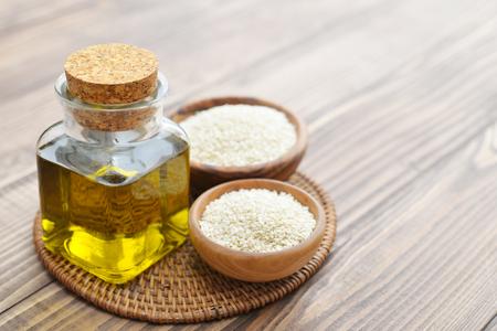 ajonjoli: Las semillas de sésamo y aceite en botella en el fondo de madera Foto de archivo