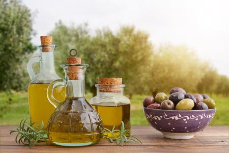 aceite de oliva: El aceite de oliva y las bayas están sobre la mesa de madera con olivos en el fondo.