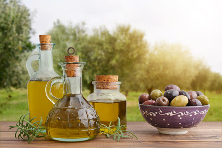 Olive oil and berries are on the wooden table with olive trees on background.