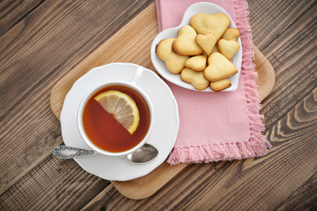 british english: Cup of tea with lemon and cookies in shape of heart on tray over wooden background