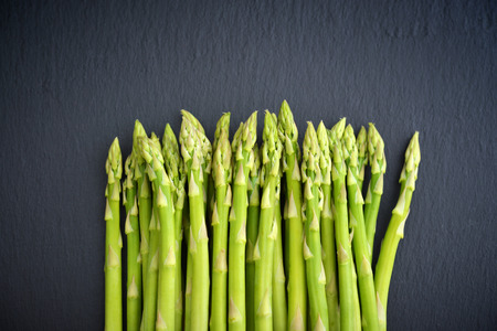 gastronomy: Bunch of asparagus on black slate background, top view
