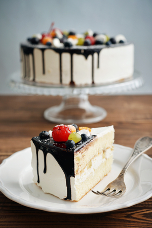 cake slice: Fruit birthday cake  with cake slice over blue background