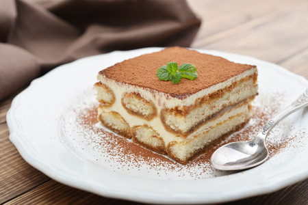 Tiramisu cake with mint on plate closeup
