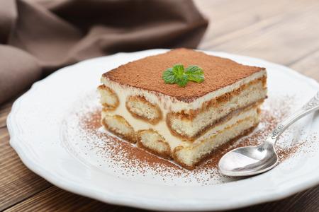 Tiramisu cake with mint on plate closeup