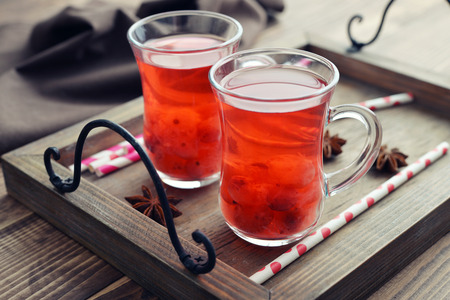 Mulled wine with fresh cranberry and anise on wooden background