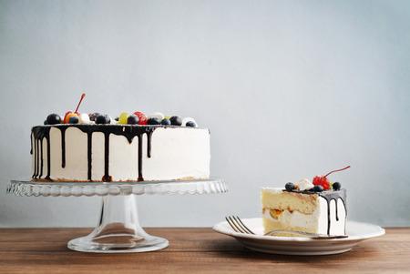 rebanada de pastel: tarta de cumpleaños de fruta con la rebanada de la torta sobre el fondo azul Foto de archivo