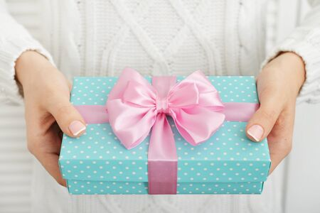 gift ribbon: Female hands holding blue polka dots gift boxes with pink ribbons