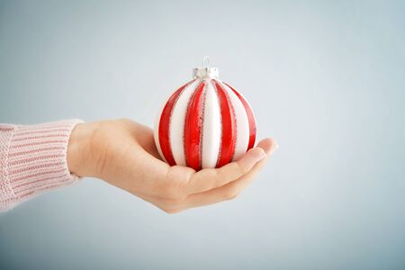 female christmas: Red christmas ball in female hand on blue background Stock Photo
