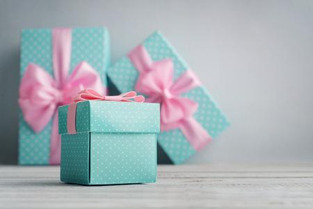 Blauwe stippen geschenkdozen met roze linten op een blauwe achtergrond