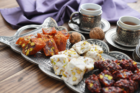 arabic food: Turkish delight with tea and metal oriental tray on wooden background Stock Photo