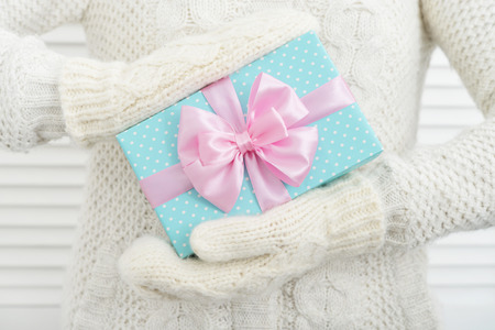 Female hands in mittens holding blue polka dots gift box with pink ribbons