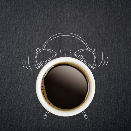 wakening: Coffee break concept. Coffe cup and sketch of alarm clock on black slate background.