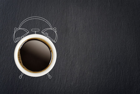 Coffee break concept. Coffe cup and sketch of alarm clock on black slate background.