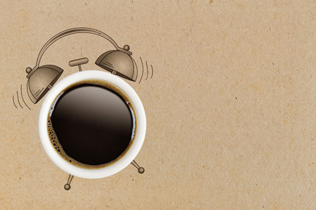 wakening: Coffee break concept. Coffe cup and sketch of alarm clock on cardboard background.