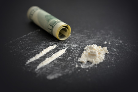 Cocaine drug addiction. Lines of cocaine and one hundred dollars banknote on black background closeup