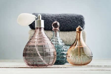 fashion background: Vintage antique bottles with perfume and stack of towels on blue background