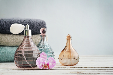 Vintage antique bottles with perfume and stack of towels on blue background