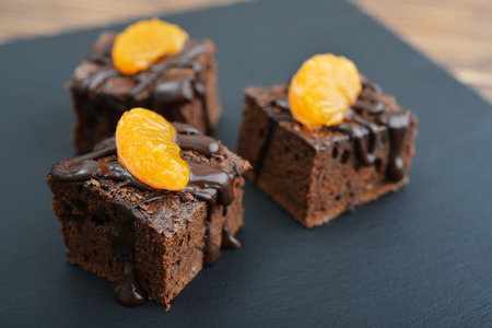 Homemade chocolate brownies with fresh oranges on black slate background