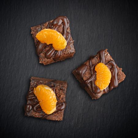 galletas: Homemade chocolate brownies with fresh oranges on black slate background, top view