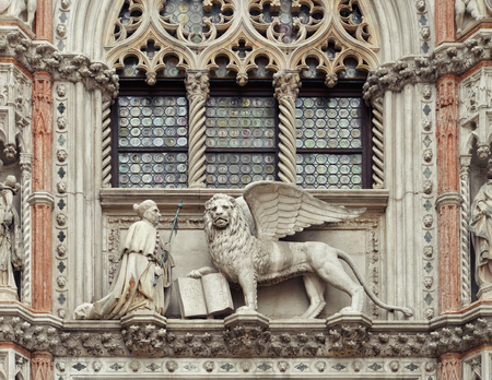 saint marco: The Doges Palace and Paper Gate (porta della Carta). Sculptures of the winged Lion and the Doge Francesco Foscari in St. Marks Square , Venice, Italy Stock Photo